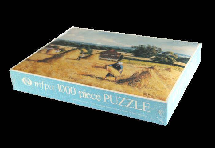 Puslespill med motiv av to mennsker som hesjer høy på en gård. Bilde.