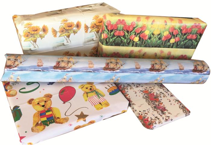 Gavepapir med blomster, seilbåt og bamser. Bilde.