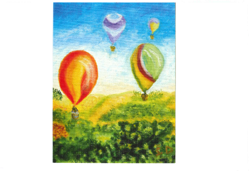 Fargerike luftballonger over grønn eng og blå himmel i bakgrunnen.